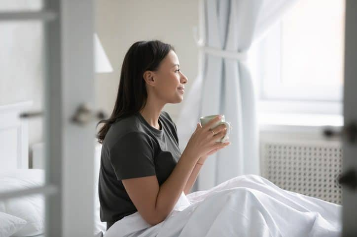 A Woman having tea in her bed and looking happy after good sleep