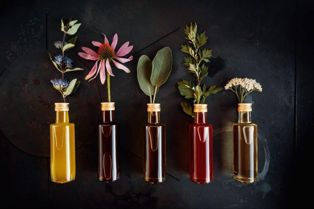 Various essential oils for sleep with flowers decorated on a dark background