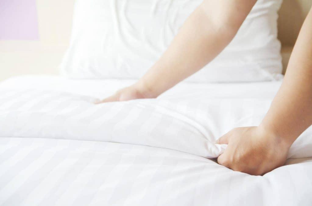 A Woman hand set up duvet on a bed