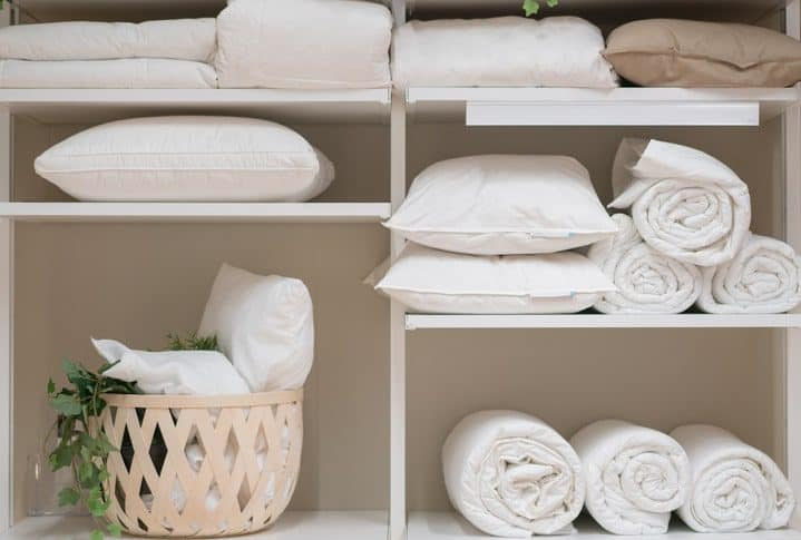bedding items such as duvet, comforter and pillows placed in a white cupboard