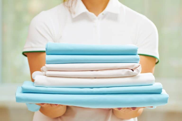 A woman holding the stack of bed sheets in hands