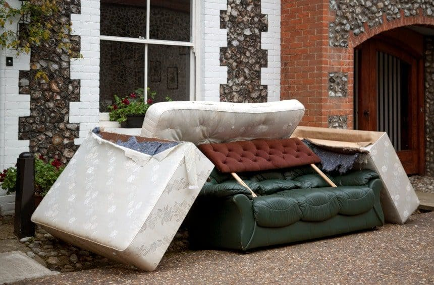A Pile of discarded mattresses and furniture on street