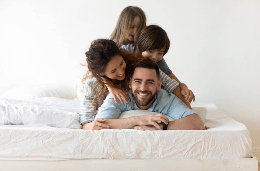 Happy young parents and small preschooler kids lying on alaskan king bed in bedroom