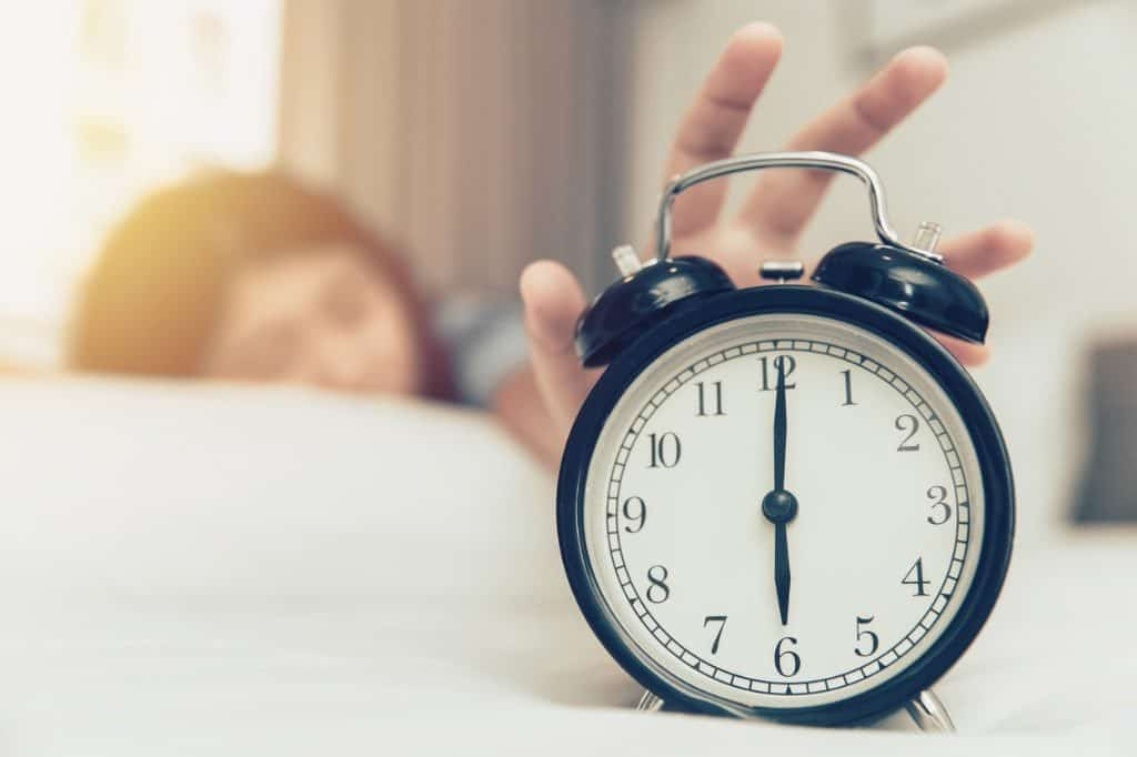 lazy to wake up girl due to oversleeping hand off alarm clock ring on bed