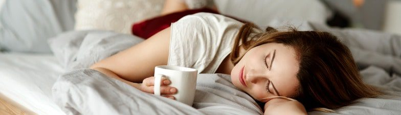 A woman with cup of coffee reclining on bed