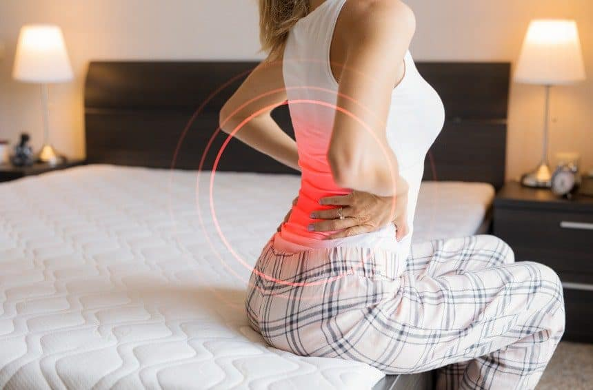 A woman suffering from back pain due to uncomfortable mattress