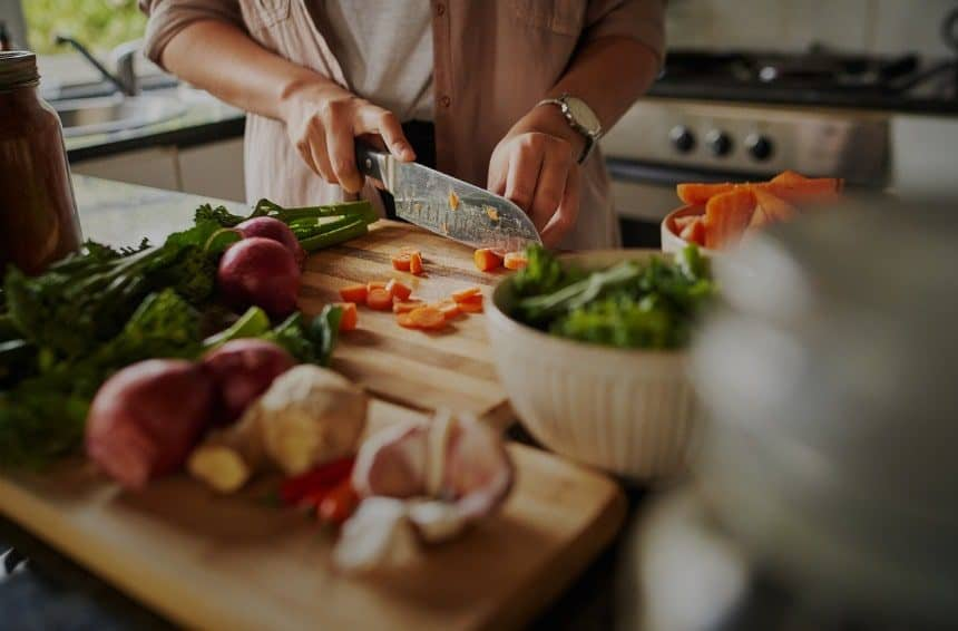 A young female chopping the fresh and healthy vegetables