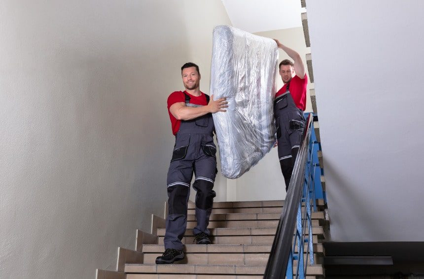 professional movers in uniform moving a mattress